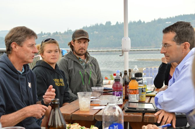 U.S. Sen. Jeff Merkley's chief of staff, Michael Zamore (far right), listens to Big Winds owner Steve Gates (far left) during a conversation about how to ensure the continued success of recreation in the state of Oregon. Paddleboarder Fiona Wylde and Northwest Rafting Company owner Zachary Collier also listen to the conversation.