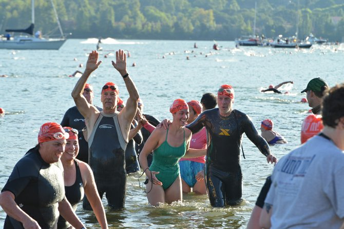 Arms are raised in joy and greeting as a wave of swimmers arrives on the Hood River Inn beach, assisted by volunteers.