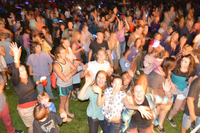 The Families in the Park crowd, above, dances to Hit Machine during the final 2013 show last Thursday. The annual August events are made possible by a long list of community sponsors.