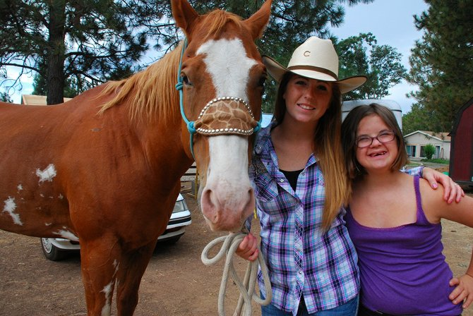 Mariah Nilson, 18, and her sister, Melody Nilson, 13, spend time with their quarter horse, Scout. Melody will be the first person with Down's syndrome to participate in the Klickitat County Fair's Western Games this week.