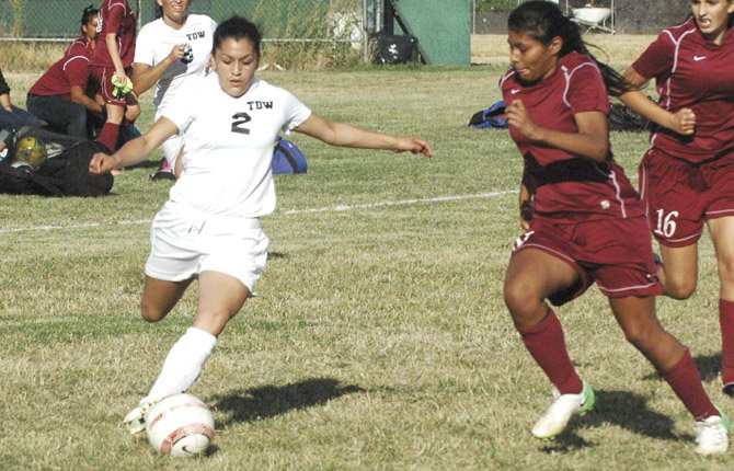 THE DALLES WAHTONKA'S Monique Mendiola (front) slips past a Mac-Hi defender for an open shot during the second half of Tuesday's non-league girl's soccer game in The Dalles. Mendiola and teammate Brooke McCall scored their first goals of the season and starting goalkeeper Ruthie Ford made three saves in leading the Tribe to a 2-0 shutout victory.