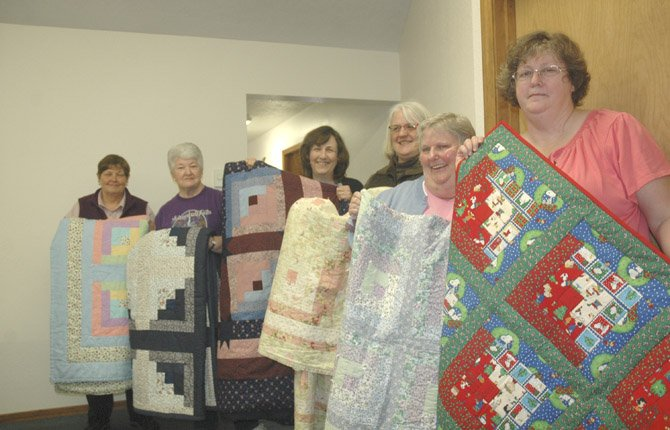 "Bridge of the Gods Quilting Group members display their fabric ""Log Cabin"" quilts at their 10th anniversary party in early 2012. For the Quilt Board version of Log Cabin, 