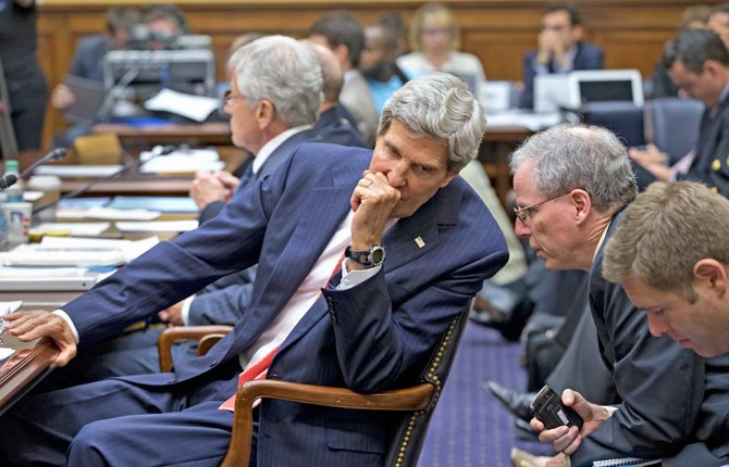 SECRETARY OF STATE John Kerry confers with U.S. Ambassador to Syria Robert Ford, right, on Capitol Hill in Washington, Sept. 4 during a House Foreign Affairs Committee hearing on President Barack Obama's request for congressional authorization for military intervention in Syria.