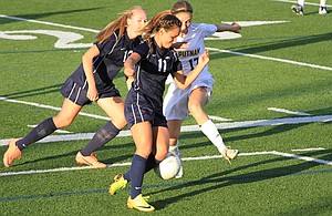 On the road Tuesday, Collete Zack (front) and Jade Schumacher team up to work around a Rex Putnam player. Zack had two goals and Schumacher one in the varsity girls' 4-0 win.