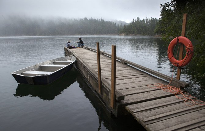 Morning mist lingers at Mountain Lake in Moran State Park in Washington state as Jennifer Imamura from Berkeley, Calif., left, and Sylvia Yang of Anacortes, Wash. sit on the dock.