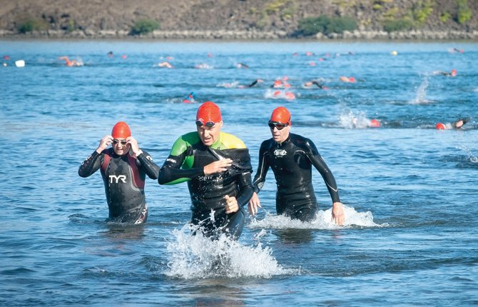 A trio of swimmers exit  the water at Riverfront Park, finishing the first leg of the Olympic course in Aluminum Man triathalon competition in The Dalles Sept. 7.	Mark B. Gibson photo