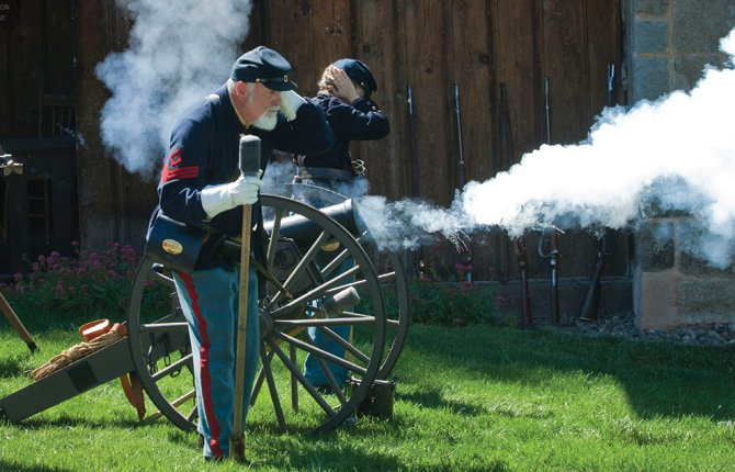 "Gunners Carson Rahrer and Paige Askew cover their ears as a civil war style cannon, left, is fired Sept. 8 at The Dalles Museum Saturday. The Idaho Civil War Volunteers were ""encamped"" at the museum Saturday, and demonstrated various civil war weapons hourly."