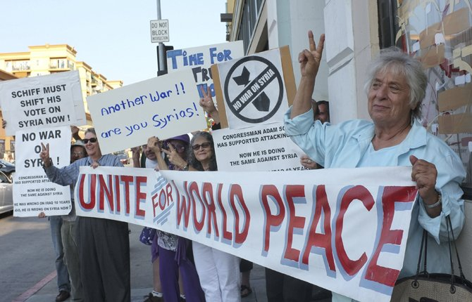 Joyce Brody, right, joins anti-war activiss rally for peace outside the offices of Rep. Adam Schiff (D-CA), a senior member of the Intelligence Committee, to urge him to vote against a possible limited military strike on Syria in Hollywood selection of Los Angeles Sept 10.   