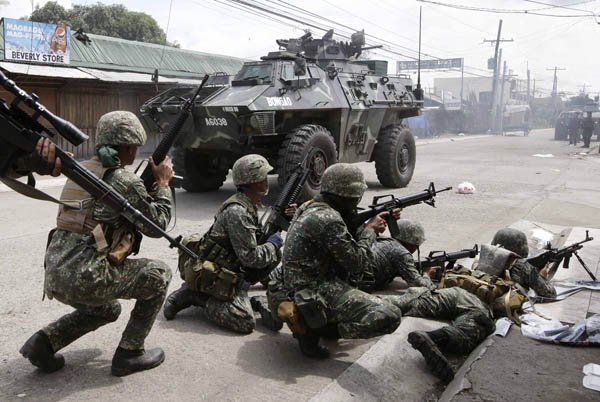 GOVERNMENTTROOPERS aboard an Armored Personnel Carrier fire at Muslim rebels in an operation to rescue scores of hostages being used as human shields by the rebels on the fourth straight day Sept. 12 at Zamboanga city in southern Philippines.
