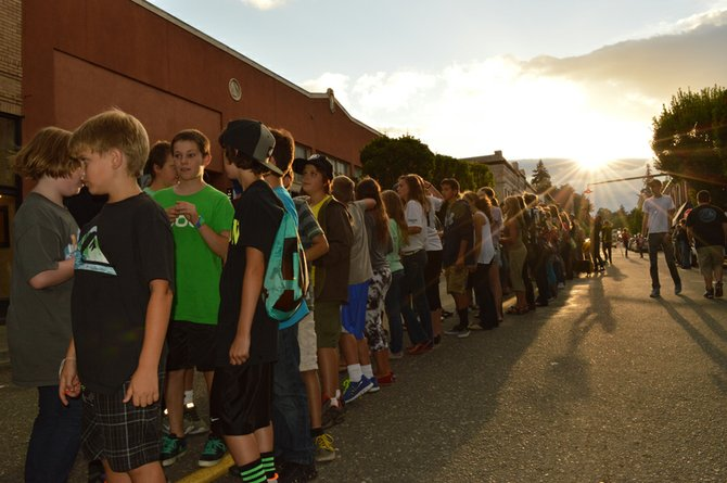 TWO LINES of people wait to do battle during the annual First Fariday Rock, Paper, Scissors tournament.