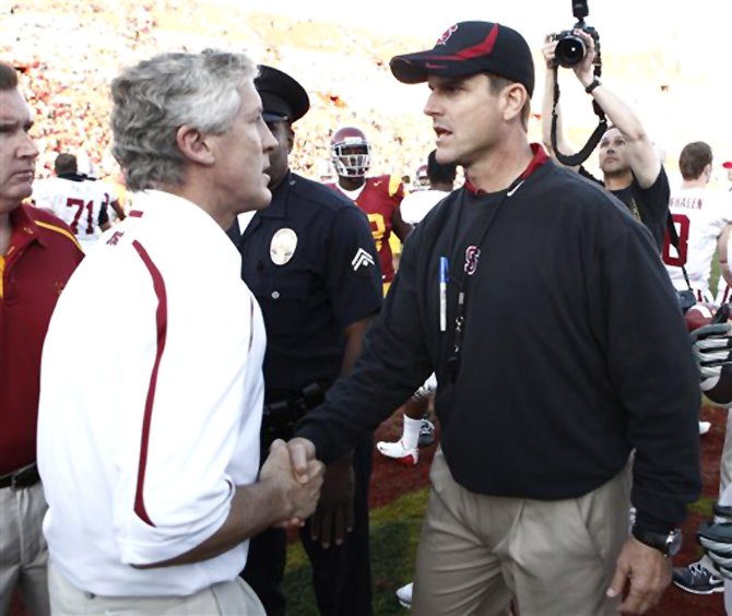 In this Nov. 14, 2009 file photo, then Southern California head coach Pete Carroll, left, shakes hands with then Stanford head coach Jim Harbaugh after an NCAA college football game in Los Angeles.