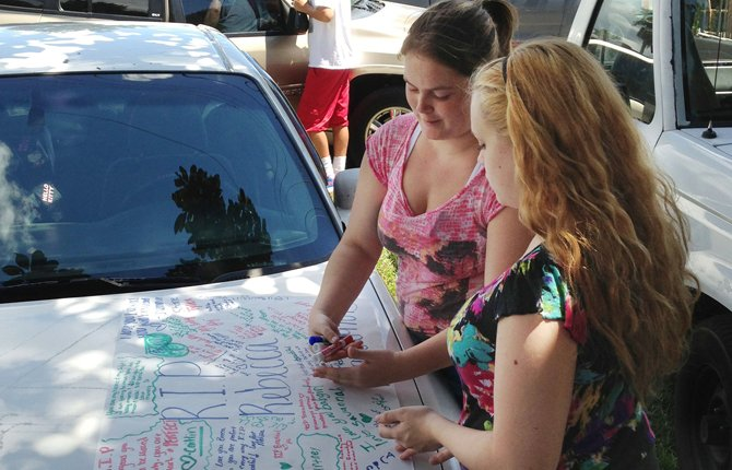 Summer Howard, 19 and Alecia Wilkins, 18, make a poster for Summer's sister Rebecca Sedwick. 