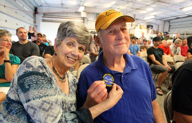 Darlyne Haynes, left, and her husband Robert Frances Haynes, hold up a patch given to him by the Search and Rescue crew Sept. 12 at the Search and Rescue headquarters in Bend. 	AP Photo/The Bulletin, Andy Tullis