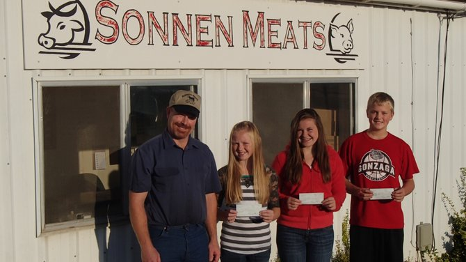 Idaho County 4-H/FFA Carcass Judging Contest winners pose with their winnings: (L-R) Norm Sonnen, owner of Sonnen Meats;  Leah Higgins, Sydney Bruner and Spencer Schumacher.