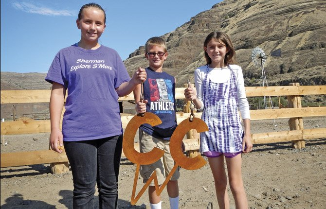 JORDAN BARRETT, Cash Helms and Isabella Mills, from left to right, hold up their brand for Cottonwood Canyon State Park. The park, with 7,800 acres and 14 miles of riverfront access on the John Day River, is set to hold its grand opening Sept. 25.  The three elementary students from Gilliam and Sherman counties submitted a similar brand design last spring. It was then chosen by popular vote on Oregon State Park's Word Press website as the icon to represent the wildland of Cottonwood Canyon.