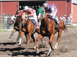 Riding Gil, Louis Zacherle, right, looks over his right shoulder at his competition coming out of Turn 4 en route to victory in a photo-finish three-quarter mile open horse race Saturday. The horse is owned by Emil Abrahamson.