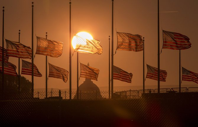 American flags surrounding the Washington Monument fly at half-staff as ordered by President Barack Obama following the deadly shooting Monday at the Washington Navy Yard today in Washington.