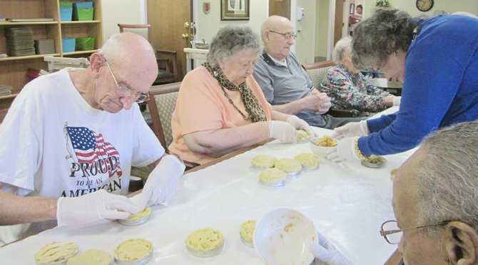 Robert Kelley, Lillyan Carr, Dewayne Carlson and Dayna Buerer (L-R) make small apple pies at Sun Terrace Assisted Living last Thursday. Debbie Smith, senior administrator, said the pies helped to spread the happiness of being American.