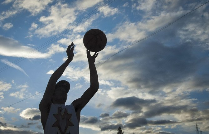 Clarence McKinley of Warm Springs shoots baskets at an outdoor court in Maupin Tuesday evening. Clouds and cooler temperatures have moved into the area, but not enough rain has fallen yet to end the risks from wildfire.