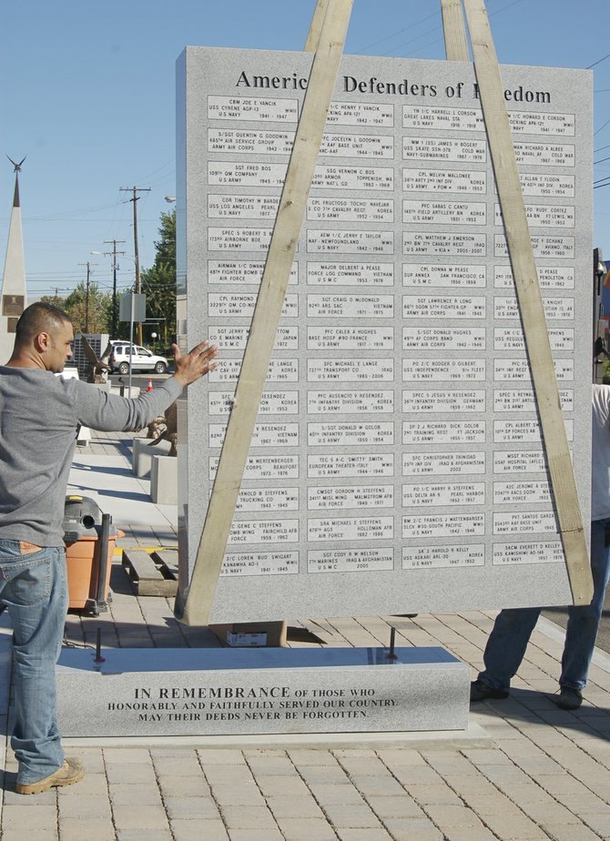 Workers install a new eight-foot high granite wall at Jerry Taylor Veterans Plaza in Sunnyside. Each granite wall has 120 names of military veterans etched on it, front and back.