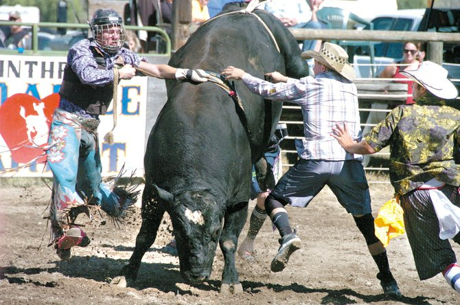 Dustin Hennigs, formerly of Okanogan and now living in Salem, Ore., got hung up during bullriding. Clowns at right, from left, are Dalton Wahl and Chris Donaldson.