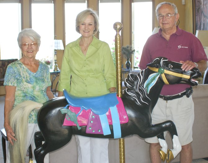"Former Sunnyside native Susan Taylor Jack (center) was in town last week to admire the work being done on her longtime travel buddy, ""Dutch"". Jack has carried the vintage carousel horse around with her since being on the 1967-68 Miss Sunnyside Court. Handling the restoration and painting on the now pristine horse are Ruth and Leroy Ganser of Sunnyside."