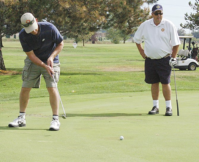 Ron Cowen of SVID putts for an eagle on hole No. 3 as teammate Jim Trull watches during the tournament last Friday.