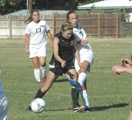 THE DALLES WAHTONKA soccer player Brooke McCall (right) fights off a midfielder to clear the ball out in action Thursday in The Dalles. In the game, McCall scored the game-tying goal to lead TDW to a 1-1 tie versus Century.