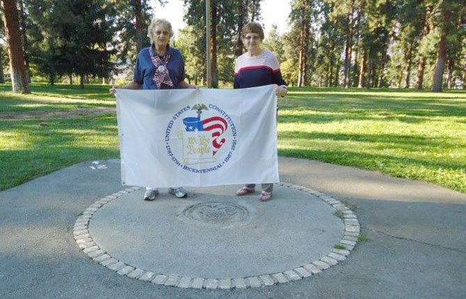 BOBBIE MILLER, LEFT, and Darlien France hold a constitutional flag above the site at Sorosis Park where a time capsule was buried 25 years ago in celebration of the 200th anniversary of the U.S. Constitution.	Contributed photo