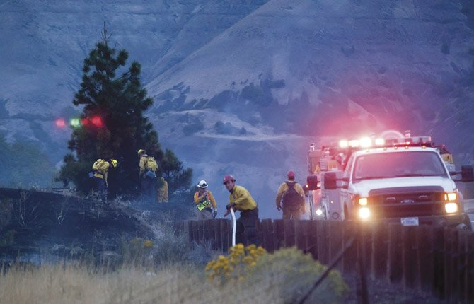 A fireman adjusts a hose on the east end of a grass fire that closed Interstate 84 and threatened several structures Friday evening. Photograph was taken from the access road to the Columbia Gorge Discovery Center.