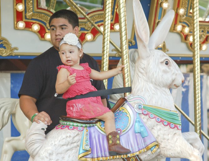 Katialia Mireles of Grandview takes her first ride on a carousel, protected by her cousin, Junior Garcia of Sunnyside. The Central Washington State Fair features one section with rides just for little children, including this attractive, turn of the century style merry-go-round. The Central Washington State Fair continues this week with daily shows, including the Walk on the Wild Side Exotic Animals and Reptiles exhibit.