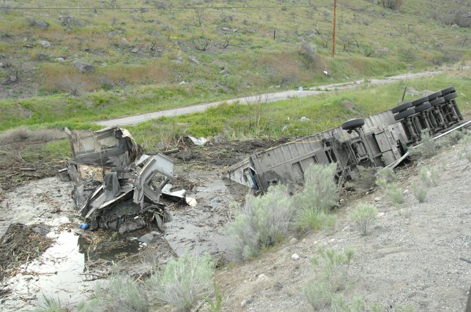 An Omak man helped pull the driver out of this tractor-trailer after it crashed into the guard rail, overturned and rolled down an embankment into a marsh.