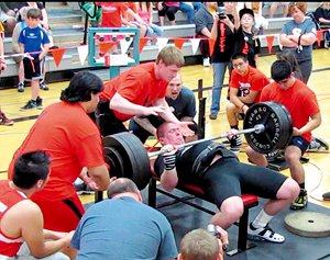 Matt Thornton of Omak's Xtreme Powerlifting Club bench presses 485 pounds, breaking the state's previous record by 55 pounds at the state tournament May 4 in Shelton. From left assisting are Sumo Sandoval, coach Jordan Lesamiz and Jacob Cutrell.