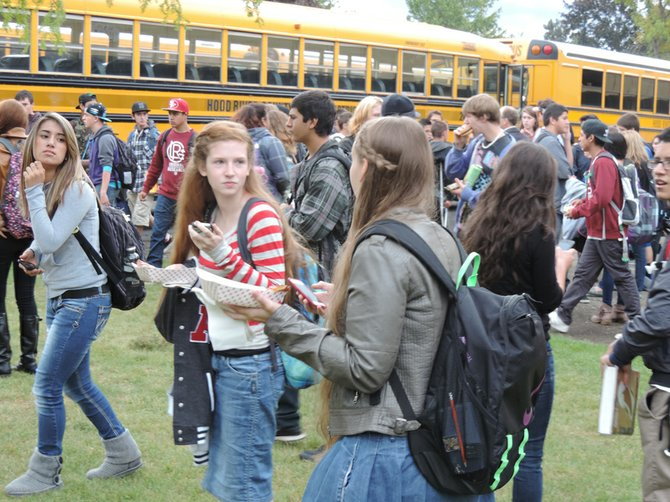 STUDENTS hurry to buses moments after Monday's bomb threat evacuation order at HRVHS. Michaela Bisbee, right, and Madison Meyer juggle cellphones and lunches as they make their way out of the east entrance. School officials report that the evacuation went smoothly, with excellent coordination by the transportation department.