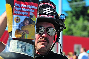 "LT. PAUL HENKE of Hood River Fire and EMS asks passers-by to ""fill the boot"" during a First Friday event last year in order to raise money for muscular dystro-phy. The department recently had its best year ever in the history of its partici-pation in the program, raising $17,500 for the Muscular Dystrophy Association."