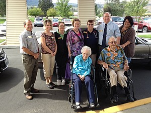 BUCK HERMANN (seated, front right) gathers for a group shot with his sis-ter-in-law Neva, 99, at the Grande Ronde Retirement Residence in La Grande, along with Grande Ronde staff and his escorts for the trip, Kelly Emerson, Hawks Ridge community relations director, center, and Melissa Stanton, resident care coordinator, far right.