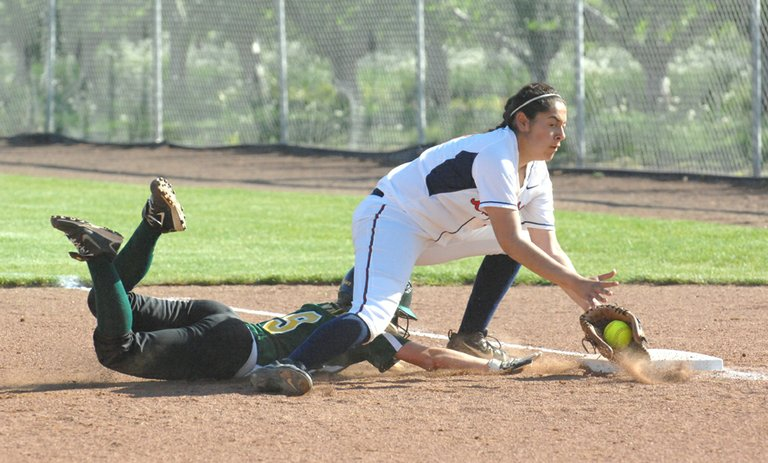Brewster's Lesli Carrillo digs out a pick off throw at first base May 7 while Quincy's Hannah Lindell slides safely between her feet.