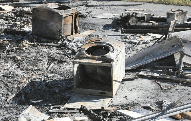 The washer and dryer dropped through the floor and into the basement of the Woods' Pateros home when it burned on May 3.