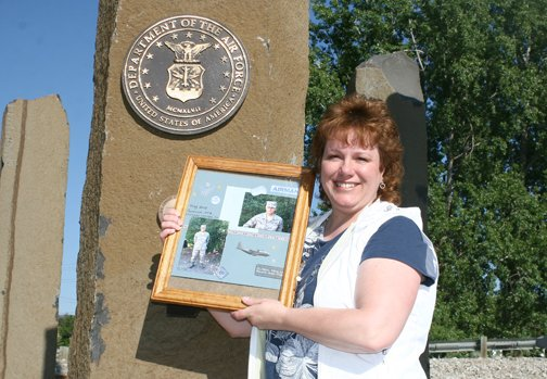 Blue Star Mothers member Julie Conkle shows photos of her son, Scott Fry, in front of the U.S. Armed Forces Legacy memorial in Tonasket.