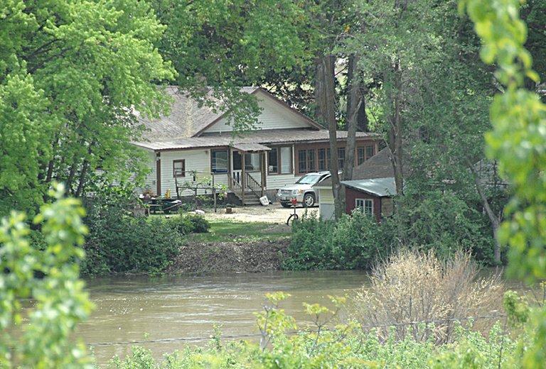 The rising OkanoganRiver nears a Tonasket home.