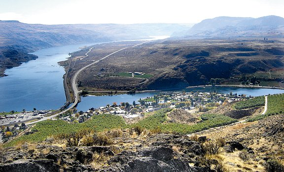 Cascading orchards give way to an aerial view of modern-day Pateros, with a view of the Columbia River south toward Wells Dam. The town was partially buried, moved and reshaped following the construction of the dam in the mid-1960s, and the city has slowly been building itself back up since then.