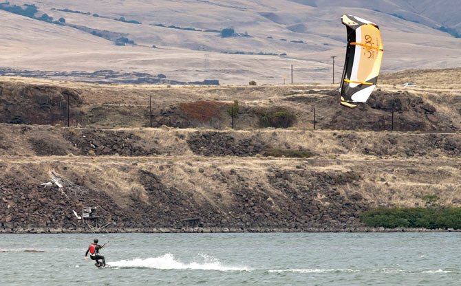 A spot of sun lights a Ken Berry's kite as he kiteboards off Riverfront Park in The Dalles Wednesday afternoon, Sept. 25.