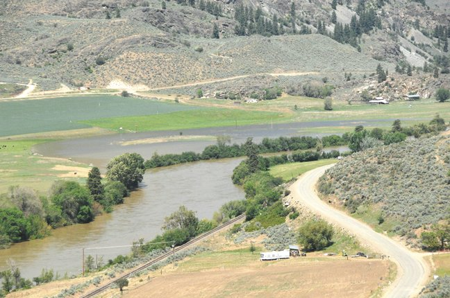 The Okanogan River swells near flood stage and into a field on Tuesday afternoon near Riverside.