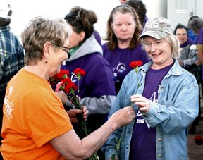 Local resident Carol Johnson, left, hands a flower to cancer survivor Rose Kuhlmann prior to the survivors' lap on Friday evening at Okanogan High School.