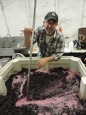 "Demonstrating the ""push down,"" Carey Kienitz, winemaker at Spring-house Cellar in Hood River, said 2012-13 are shaping up as prime wine years in the Gorge. Kienitz stirs the 1.5 tons of merlot grapes in one of 18 fermenting tanks that will fill the winery by the end of this weekend, one of the busiest times for wines in the area."