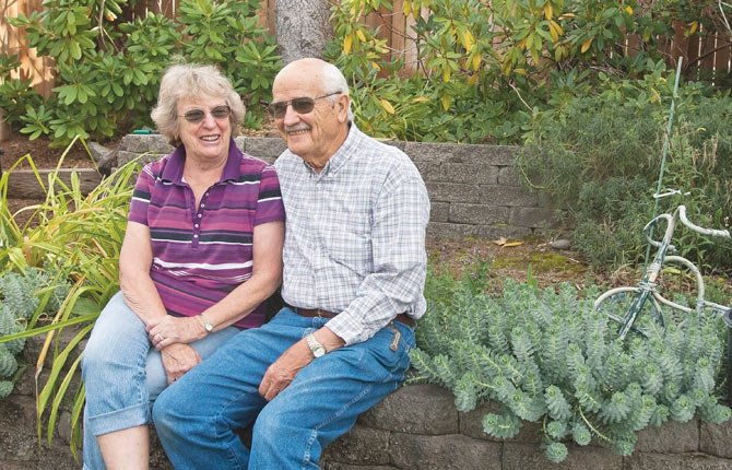 LAURANCE AND Ava Sue Kerr sit on a retaining wall in a corner of their garden. They built the house on 16th street about 40 years ago and it is now the base where they make travel and community service plans.