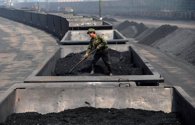 FILE - In this Wednesday, July 31, 2013, file photo, a worker levels the coal on a freight train in Taiyuan in northern China's Shanxi province. Coal has been the dominant fuel for power generation for a century because it is cheap, plentiful, and easy to ship and store. But it emits a host of pollution-forming gases and soot particles, and double the greenhouse gas emissions of its closest fossil fuel competitor, natural gas.
