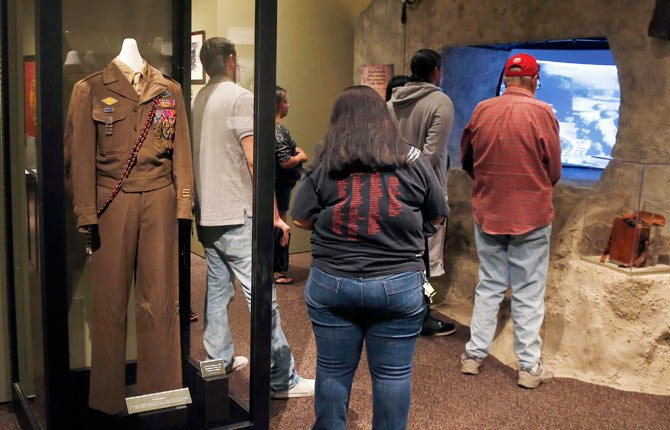 A WORLD War II uniform with the bandolero worn by Comanche Code Talker Charles Chibbity is on display in an exhibit about the code takers at the Comanche National Museum & Cultural Center in Lawton, Okla, Sept. 26. Pictured are people watching a video on the D-Day invasion at Normandy.