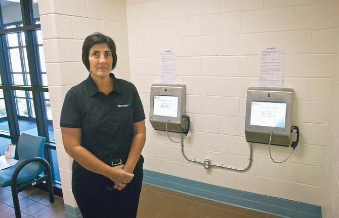 THERESA CRIM,  a representative from Telmate, stands by two computer screens in the jail lobby that the telcom service provider installed to facilitate visits between inmates and friends or family members. The new system was launched Tuesday and allows visits to be arranged on site or remotely.