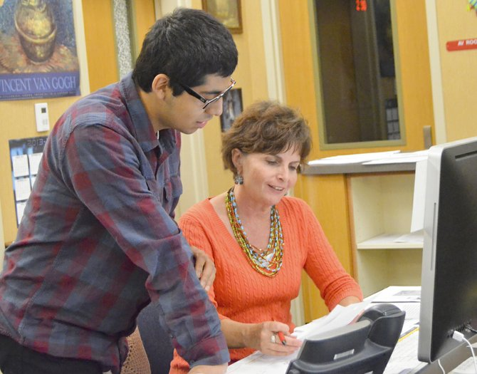 Sunnyside High School teacher librarian Karen Hutchinson enjoys interacting with students on a daily basis. Here, she helps a student with a document for honor society.